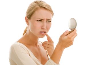 口元の乾燥を鏡で見て気にする女性