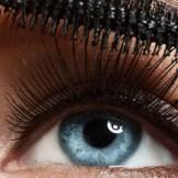 長い睫毛にマスカラを塗る青い目の女性
