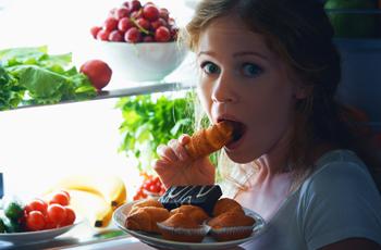 深夜に冷蔵庫を開けて甘いものを食べようとしている女性