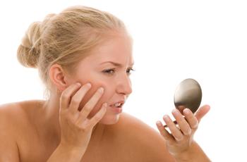 鏡で顔をチェックする女性