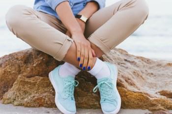 スニーカーで足を組む女性