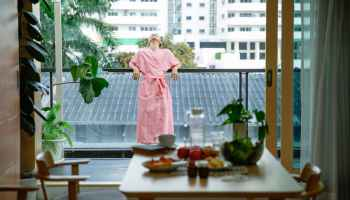 woman standing on balcony and enjoying morning time