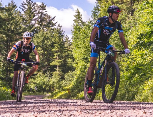 Two men riding mountain bikes on gravel in the Chequamegon 100 about to turn onto Seeley Pass