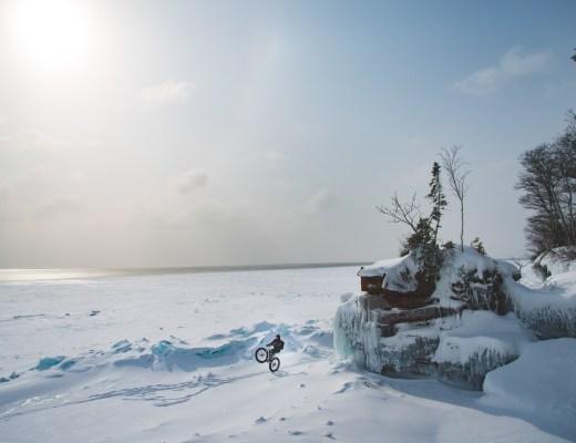 Person riding wheelie on fat bike on ice of Lake Superior near shore