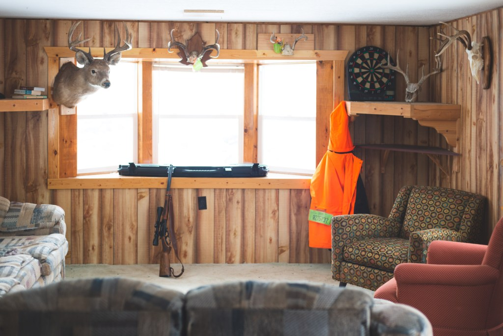paneling covered walls and mounted deer with rifle leaning against a window in a trailer