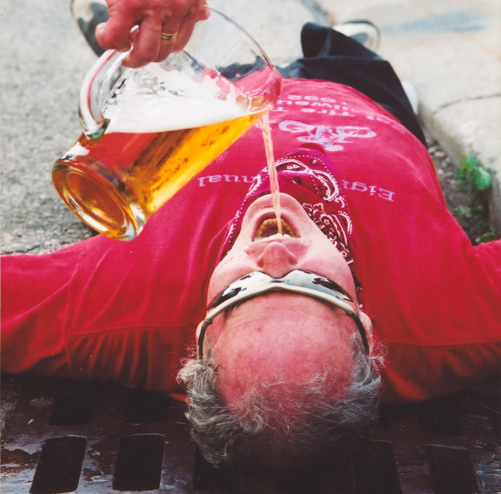 someone pours beer from a pitcher into Phil's open mouth as he lies on his back in the gutter.