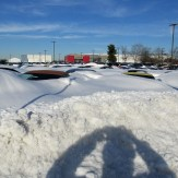 CORVETTES, YOU CAN SEE A FEW INCHES OF THEIR ROOFS ABOVE THE SNOW DRIFTS.