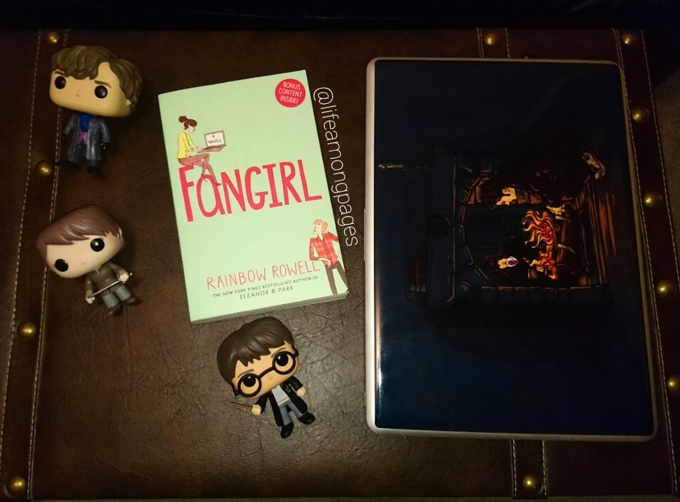 My copy of Fangirl, beside items from fandoms I Fangirl over. Including my Harry Potter, Sherlock Holmes and Arya Stark pop vinyls. And my laptop with its 10th Doctor and Hermione Granger laptop skin.