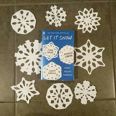 Let It Snow by John Green, Maureen Johnson and Lauren Myracle book lying beside paper snowflakes