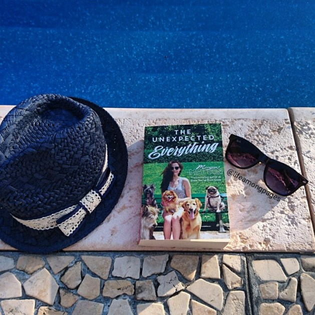 The Unexpected Everything, lying on pavement beside a pool, with sunglasses and a hat sitting on either side of the book.