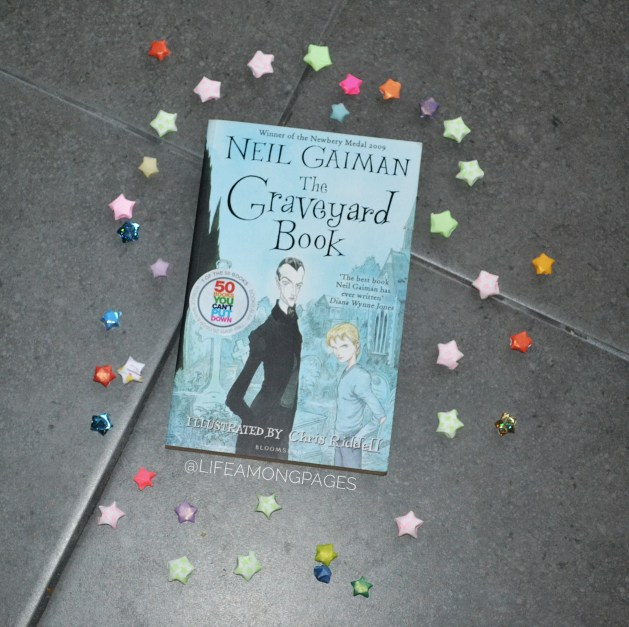Top Ten Tuesday - The Graveyard Book by Neil Gaiman lying on the ground surrounded by paper stars