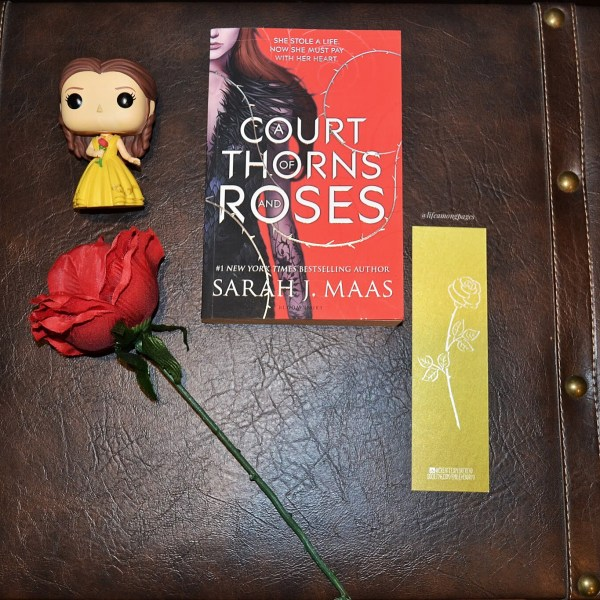 A Court of Thorns and Roses by Sarah J. Maas, with a Belle (from Beauty and the Beast) pop funko with a fake red rose and a golden rose bookmark