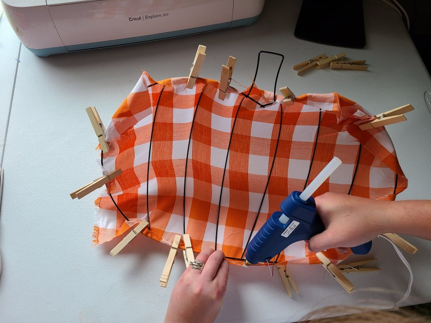 Adding hot glue to the fabric to wrap around the bottom ring on the Dollar Tree pumpkin wreath form.