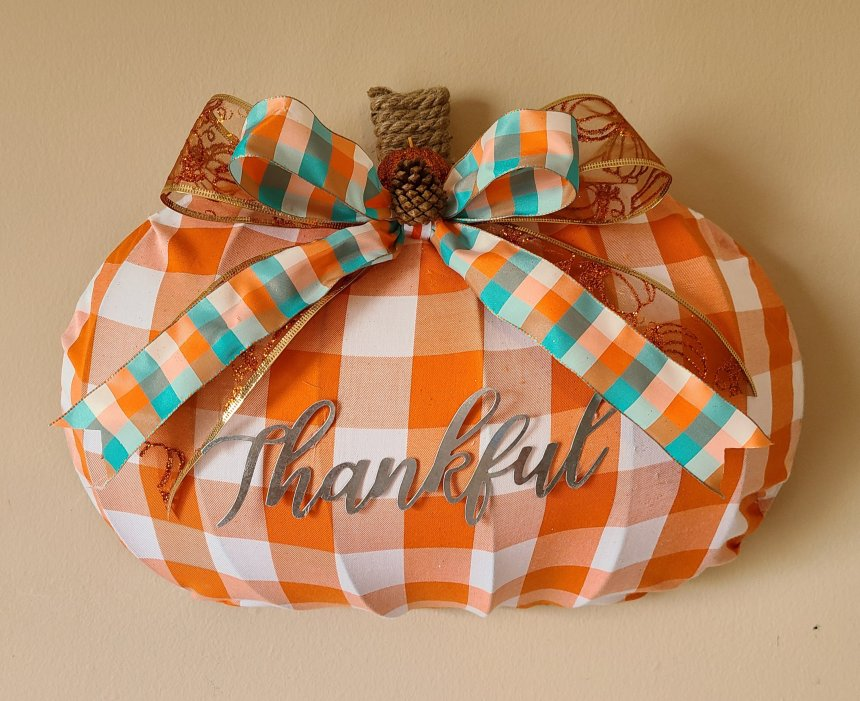 """Dollar Tree pumpkin wreath form covered with orange and white buffalo check fabric, galvanized metal """"Thankful"""" in the center, nautical rope wrapped around the top to create a stem, and a teal, orange, & white bow on top of orange and gold glitter ribbon bow."""