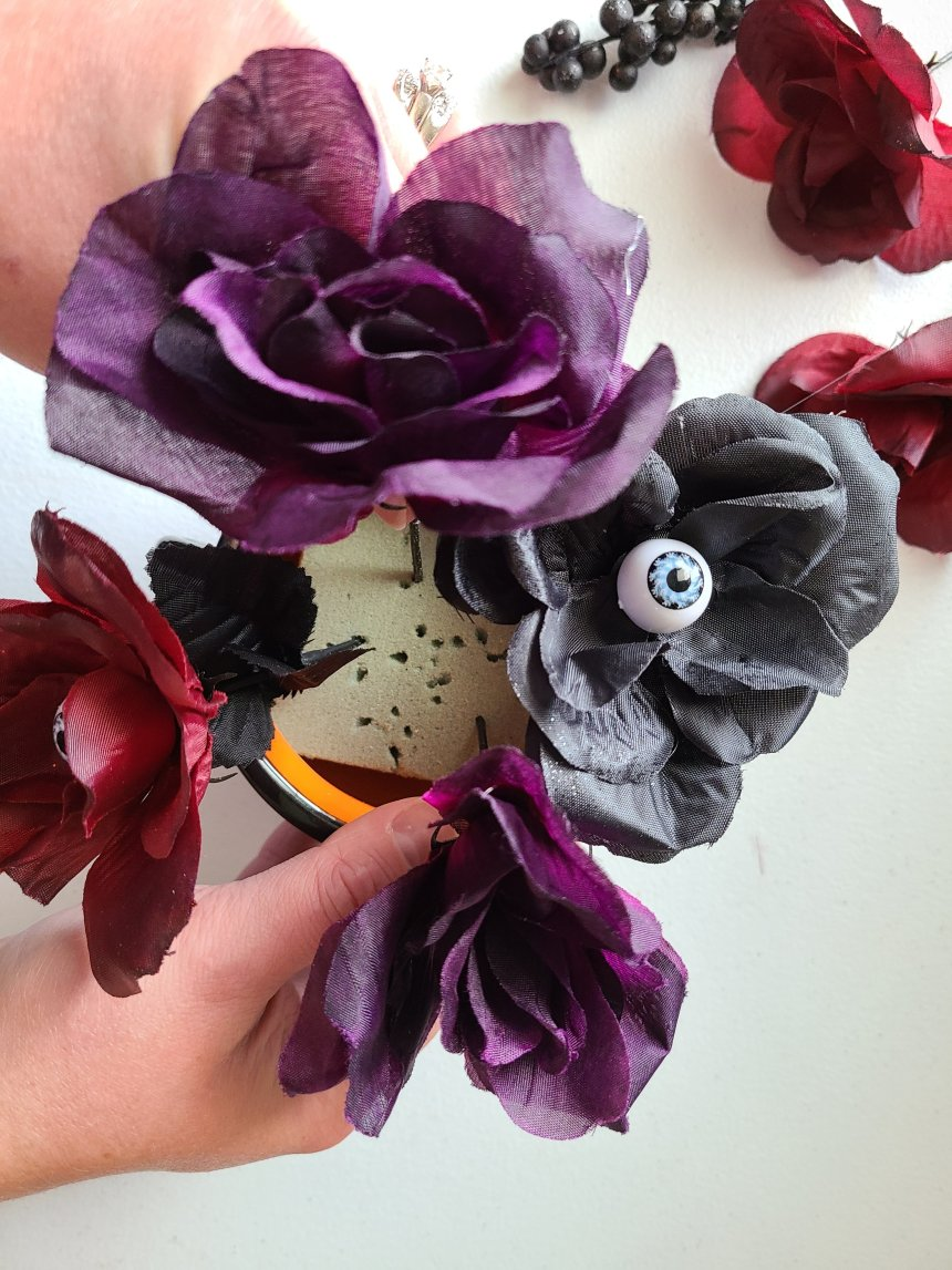 Adding plum colored faux roses to the floral foam inside the quick and easy Halloween centerpiece.