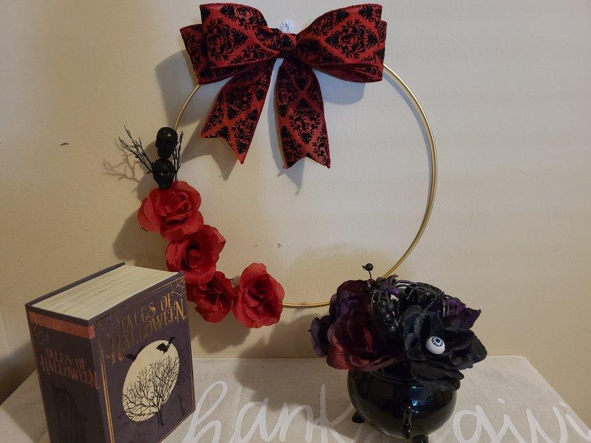 "Halloween hoop wreath with other Halloween decorations in front, black cauldron centerpiece & Halloween ""Tales"" book."