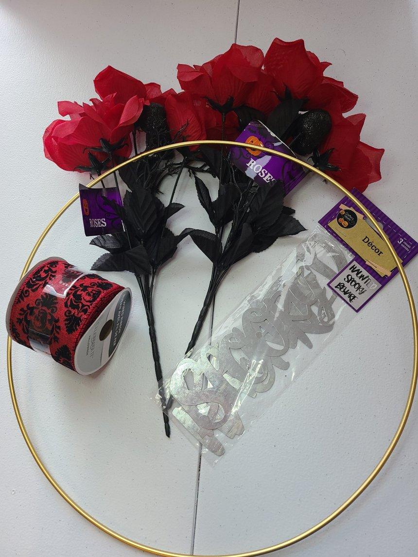 "Supplies needed for a Halloween hoop wreath: gold 14"" hoop, 2,5"" burgundy and black velvet ribbon, two stems of roses with black glitter skulls."