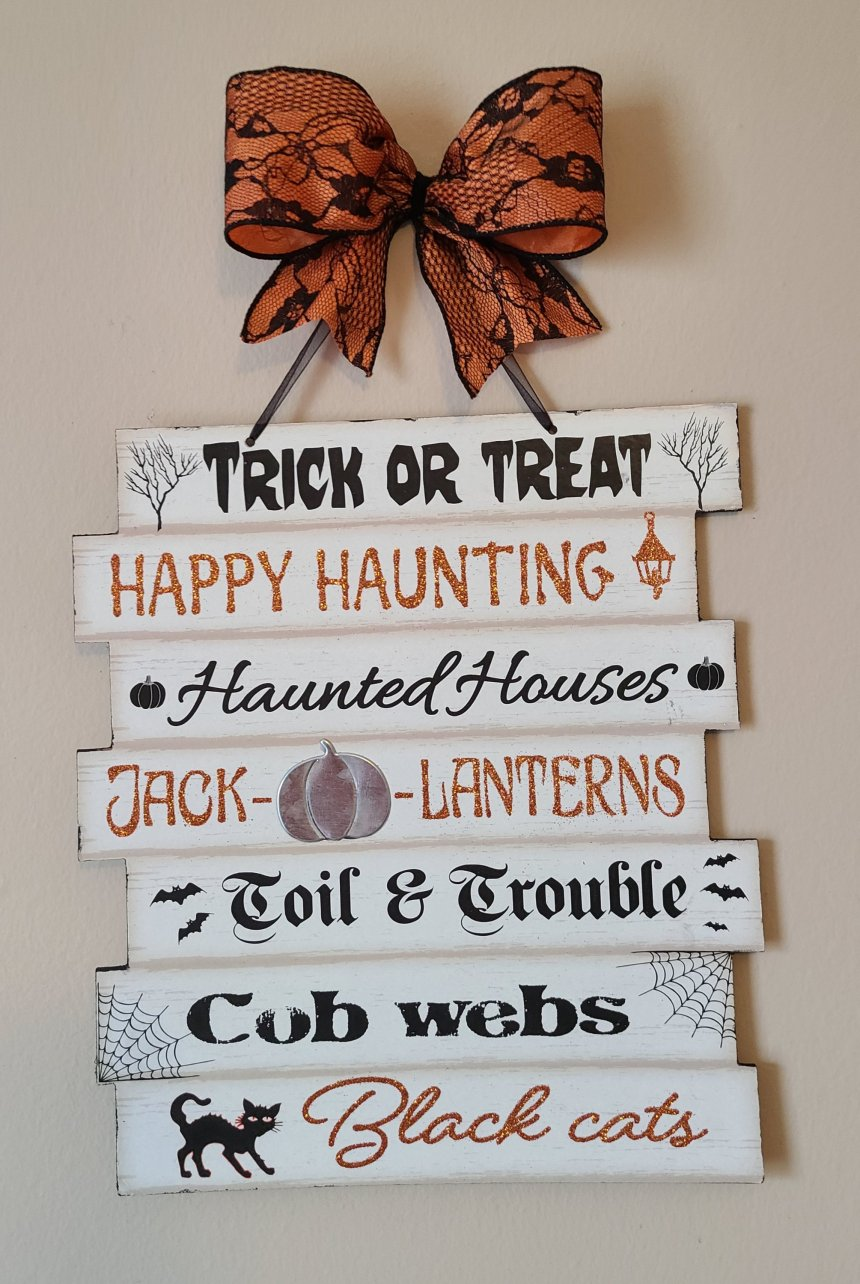 """Upcycled Halloween Dollar Tree sign with added orange 2.5"""" ribbon with black lace made into a bow at the top, black organza ribbon hanger, with Halloween words on sign."""