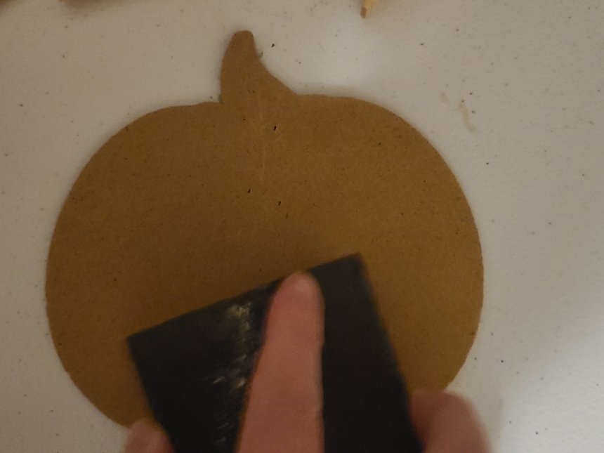 Pumpkin removed from Dollar Tree sign being sanded before it's painted and placed on the Halloween pumpkin wreath.