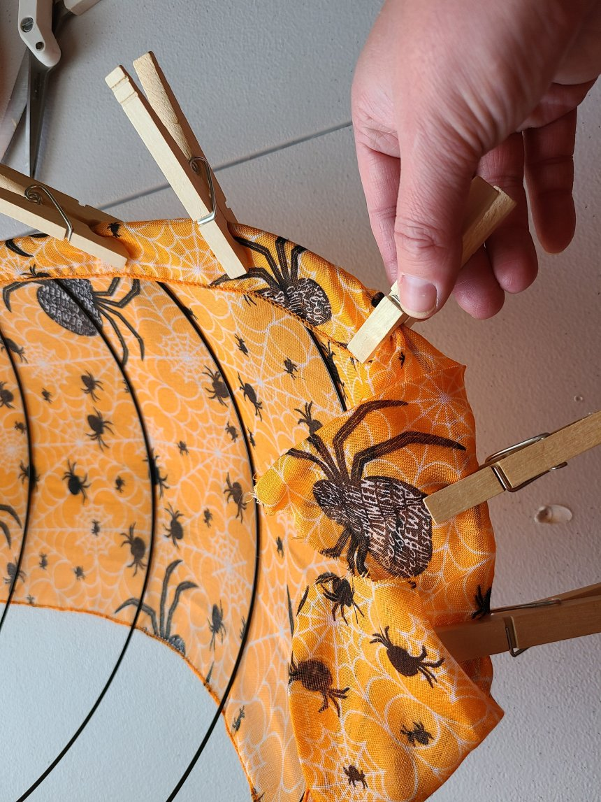 Clothespins are being added to hold the scarf on the Halloween pumpkin wreath form.