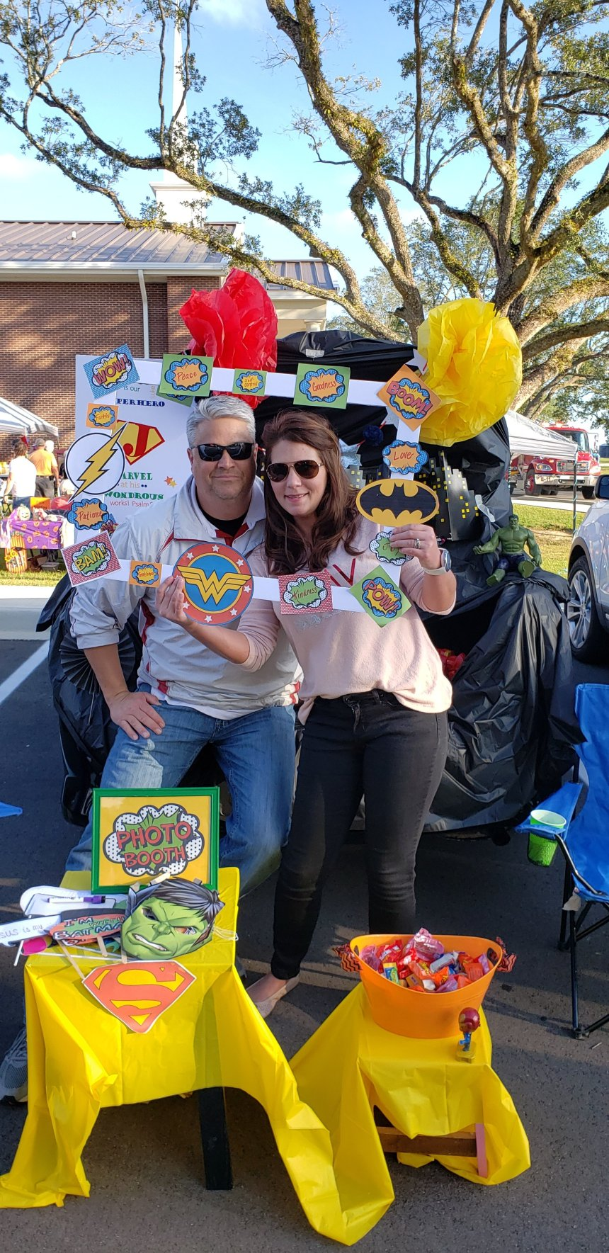 """Superhero trunk or treat idea: a photo booth. My husband & I are holding a """"Polaroid"""" frame made with superhero logos and comic book images around it. In front is a small table with a photo booth sign with masks and other props that can be used in it. Another table holds the candy that the kids can choose from."""