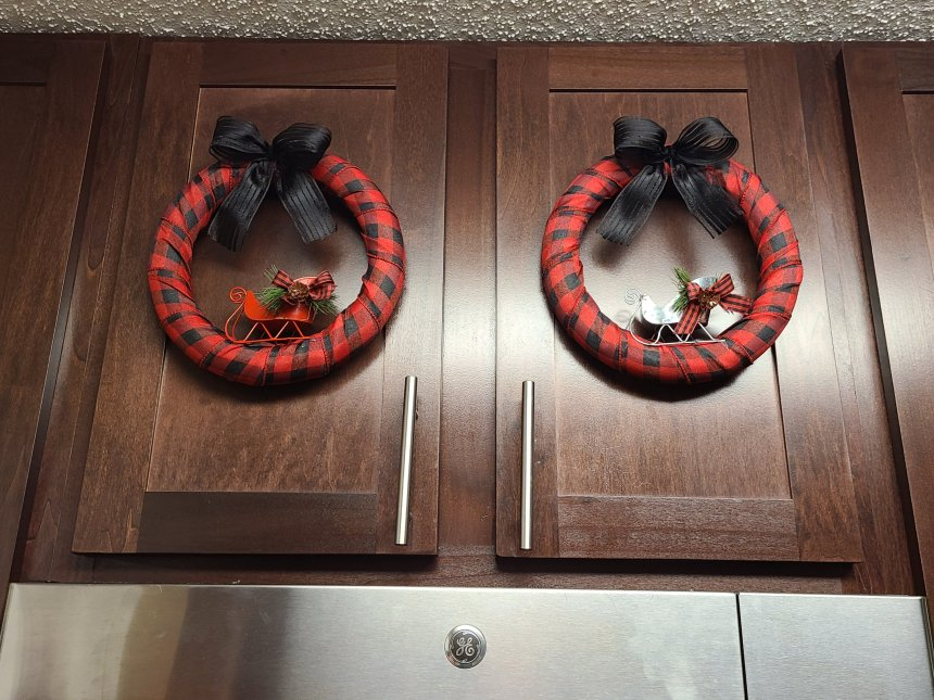 Two Christmas buffalo check wreaths on cabinet doors.