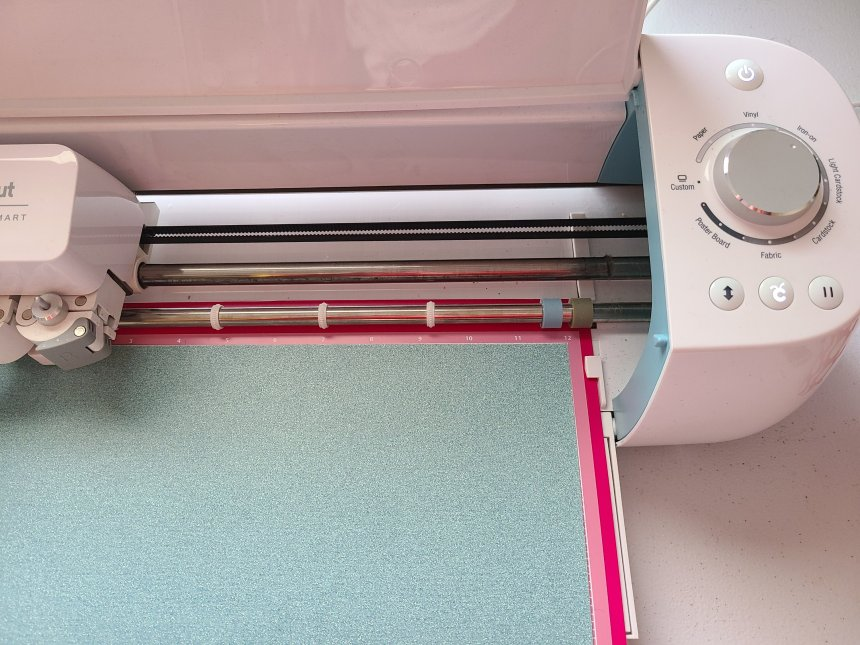 Load HTV in to the Cricut to cut for Valentine's Day doormat.