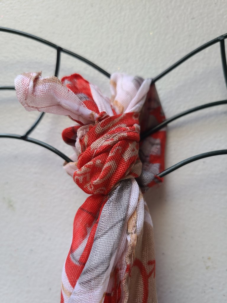 Tie scarf in a know on the top of the DIY Valentine's heart wreath