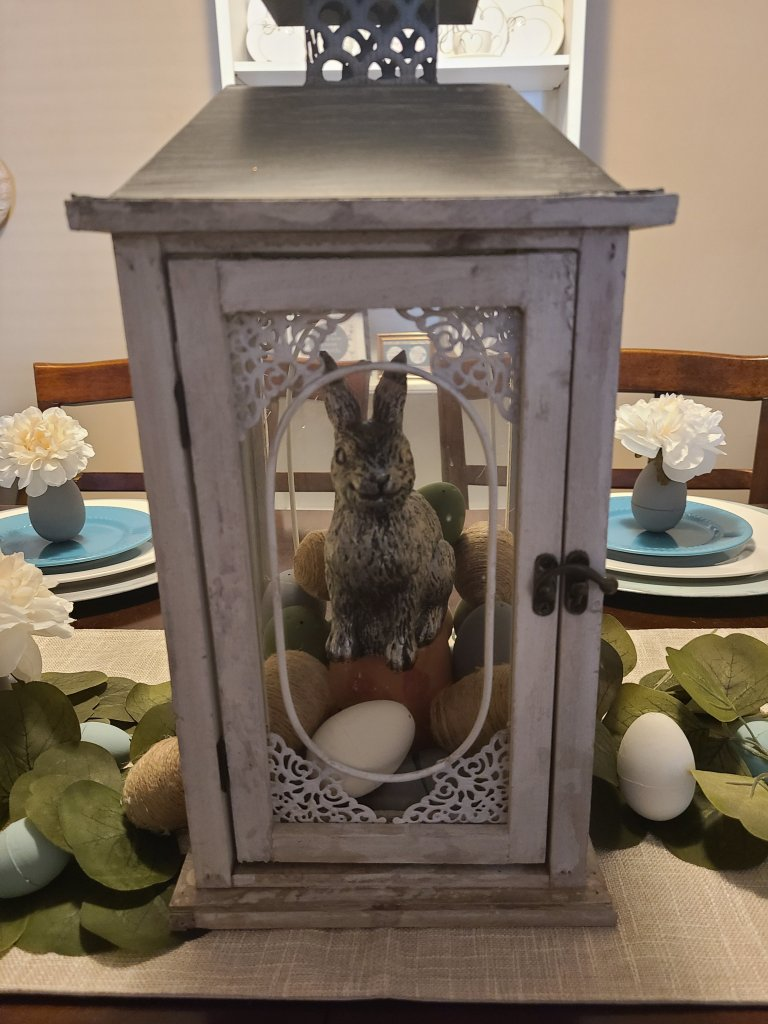 Lantern filled with chalk painted eggs, a terracota pot, & a silver rabbit on top of it on an Easter tablescape.