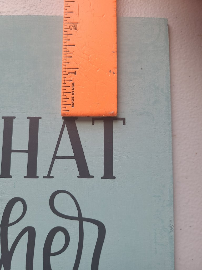 Ruler measuring the distance between the top right letters and the top of the Dollar Tree Cricut sign.
