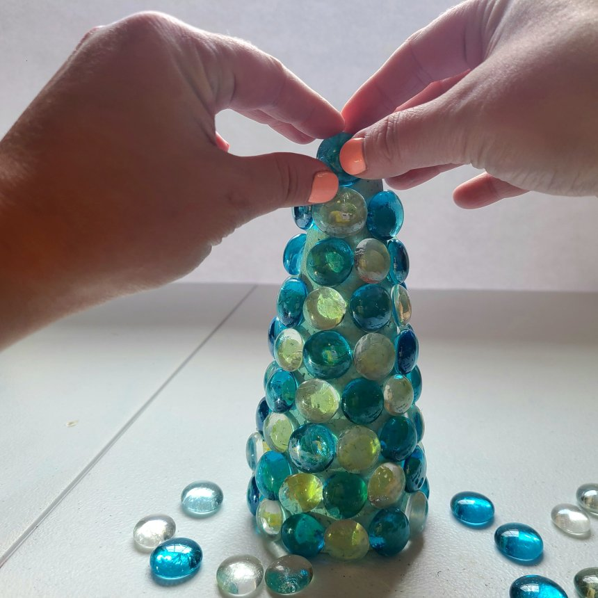 Hot glue the gems all the way to the top of the nautical topiary.