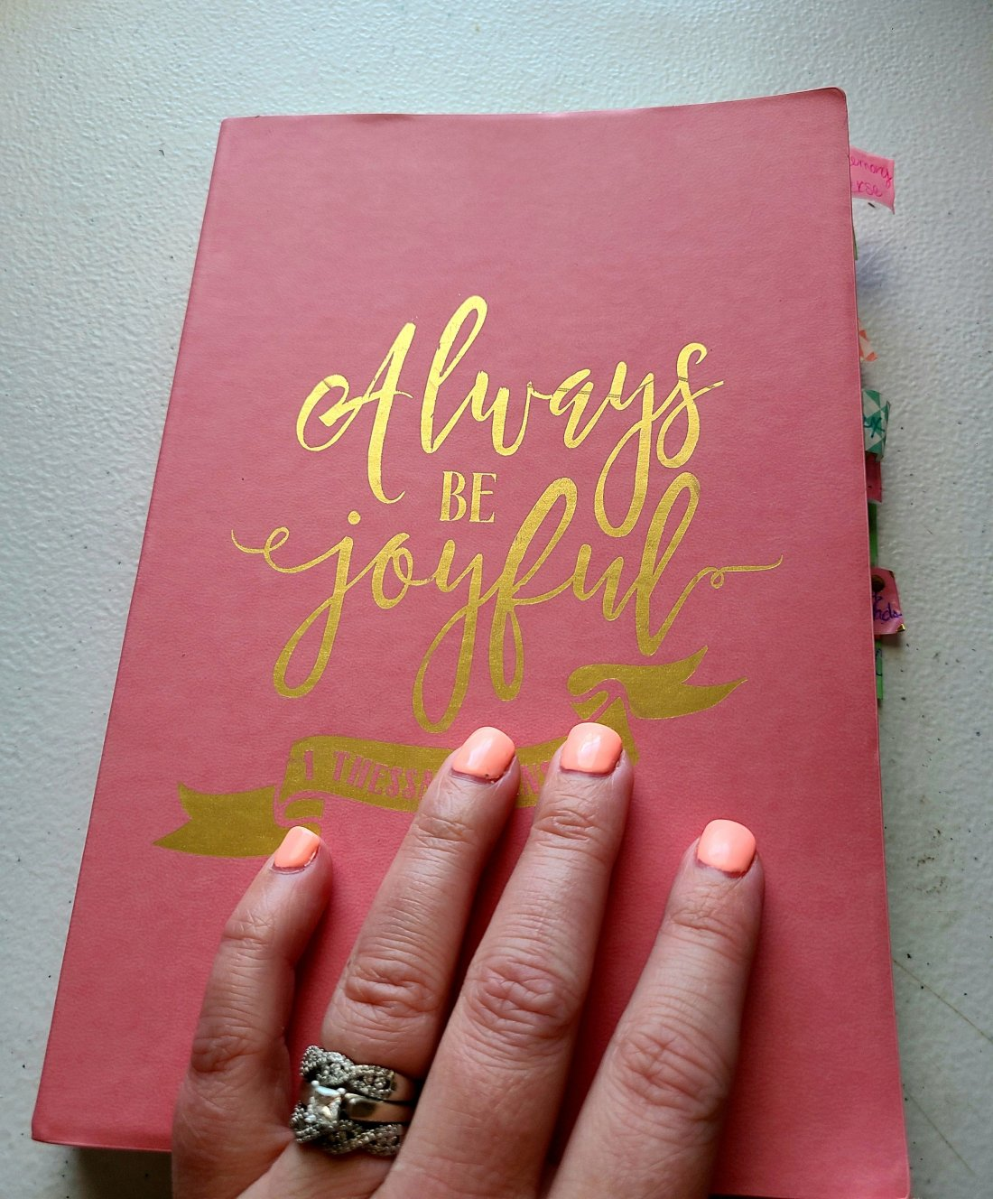 """Cover of my prayer journal. A pink notebook with """"Always be joyful"""" written in gold."""
