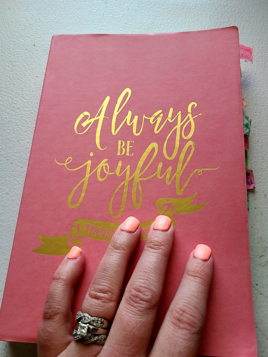 "Cover of my prayer journal. A pink notebook with ""Always be joyful"" written in gold."