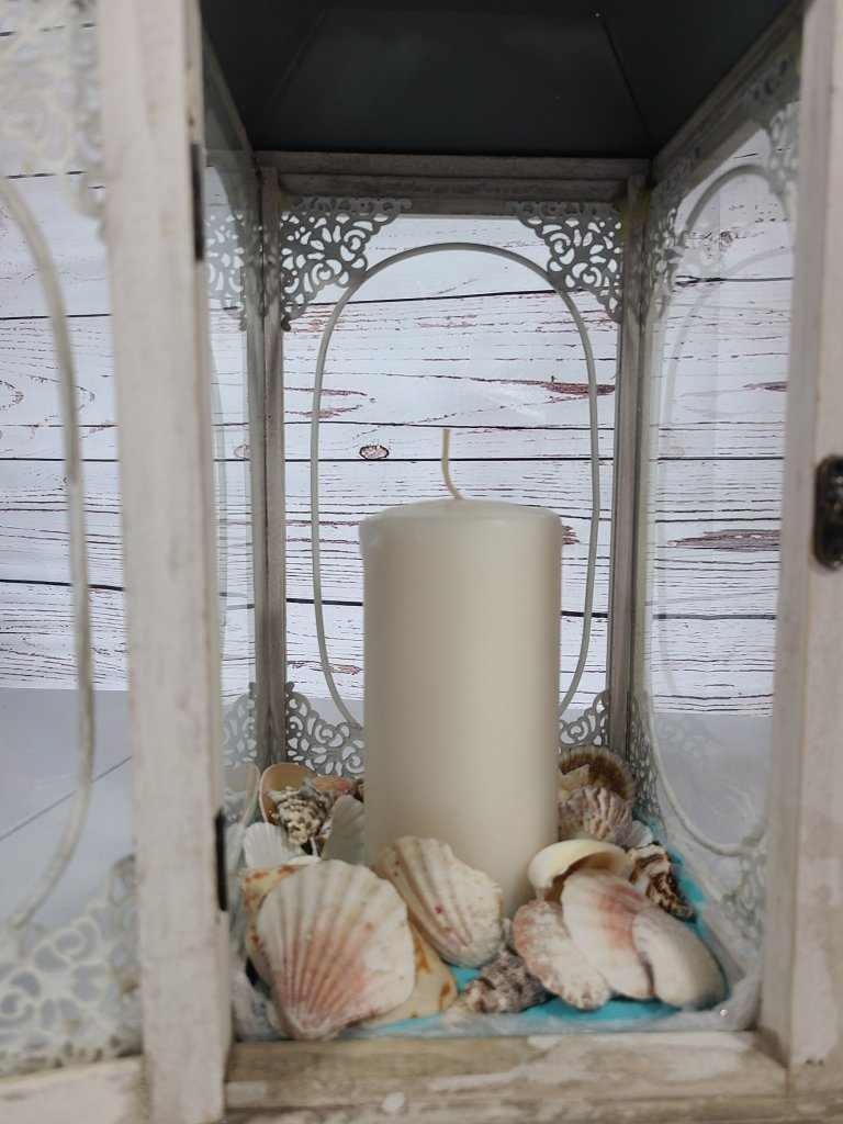Layer more seashells around a white candle.