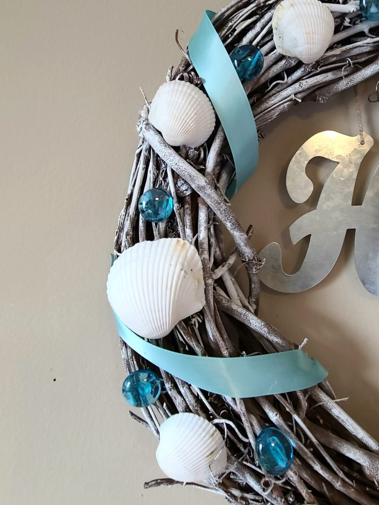 Close up picture of the side of the beach wreath. Grapevine form with white seashells, blue gems, and satin ribbon.