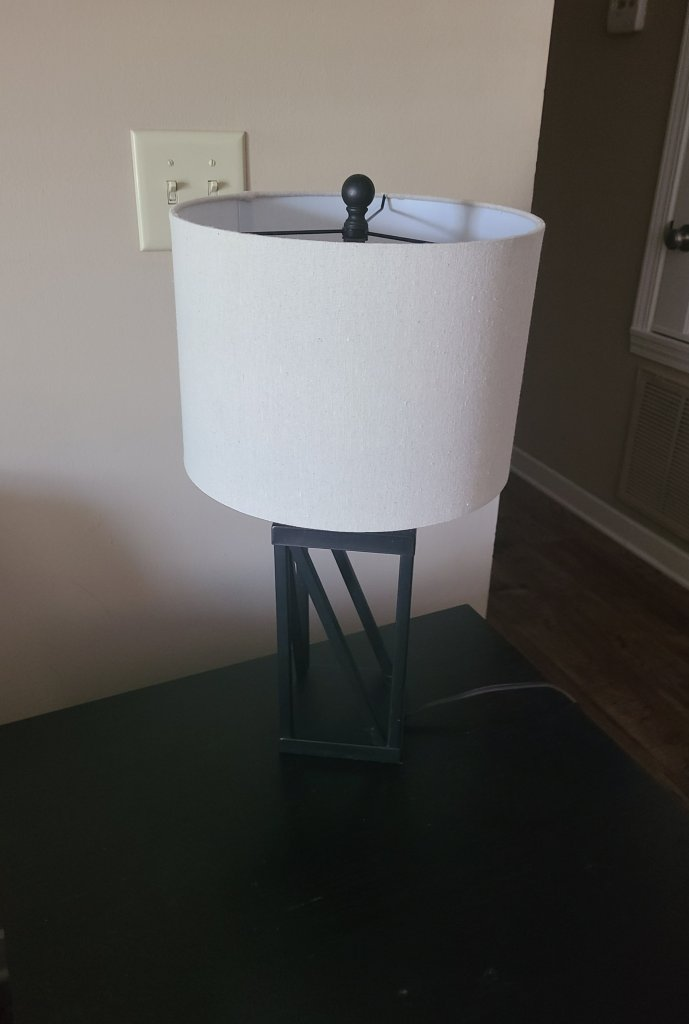 A lamp with a black geometric base with a tan lamp shade. It is sitting on a black side table that will hold the quick summer vignette.