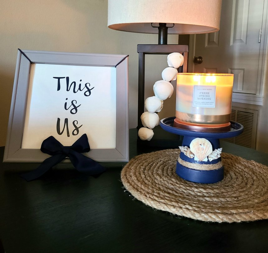 "Quick summer vignette with rope placemat with nautical candleholder with a three-wick candle on top. A black lamp with seashell additions. Next to those is a gray framed sign that says, ""This is Us."""
