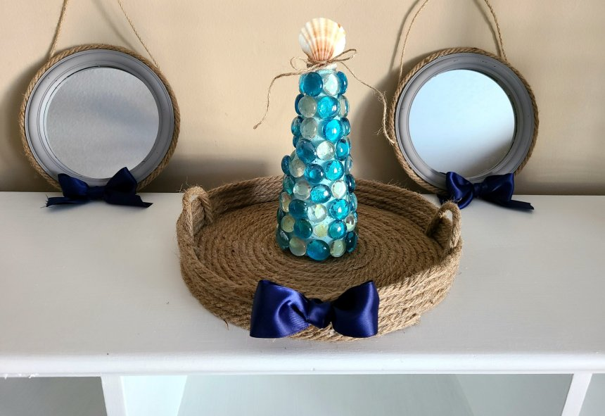rope tray with navy ribbon on the front. Inside is a glass gem topiary with a seashell topper. Nautical rope mirrors are on each side of the tray.