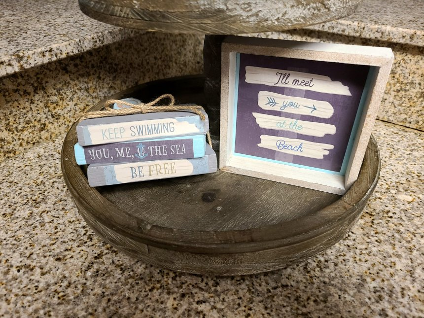 Upcycled sign on the bottom of a two tier tray. Next to that is 3 faux books tied with twine.
