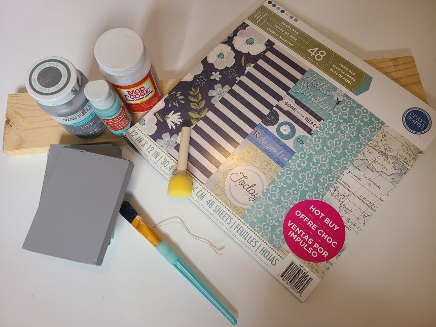 Supplies needed for making faux books, scrapbook paper pack, paint, wood