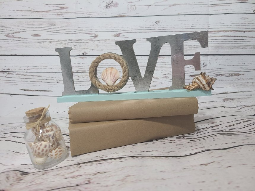 LOVE table-top sign with a robin's egg blue base, galvanized metal letters, & a nautical rope wrapped on the O. A seashell is in the middle of the O and a conch shell is on the end of the base in front of the E