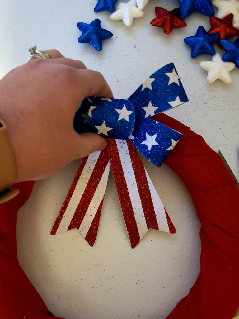 Hot gluing red, white, and blue ribbon to  DIY patriotic wreath.