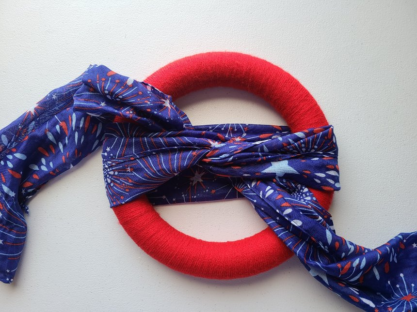 Scarf and yarn patriotic wreath wrapped in red yarn, blue scarf wrapped around the middle and crossed in the middle in the first step of tying it
