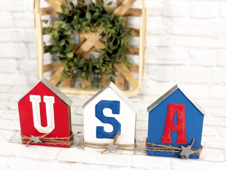 """Three small basic house shaped wood pieces. One painted red with a """"U"""" on it, white with """"S"""", and blue with """"A."""" Each house has what looks like a metal roof and twine wrapped bottoms with a glitter silver star attached."""