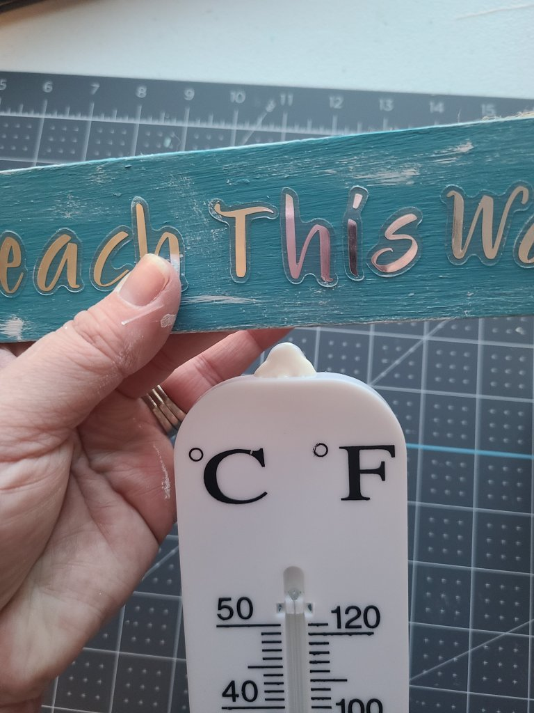 """Wood glue added to the top of large outdoor thermometer with wood arrow painted teal. """"Beach this way"""" printed on the arrow for use as a porch decoration."""