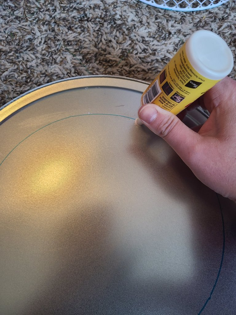 Squeezing super glue on the bottom of the pizza pan just inside the Sharpie drawn circle to attach the top of the DIY side table.