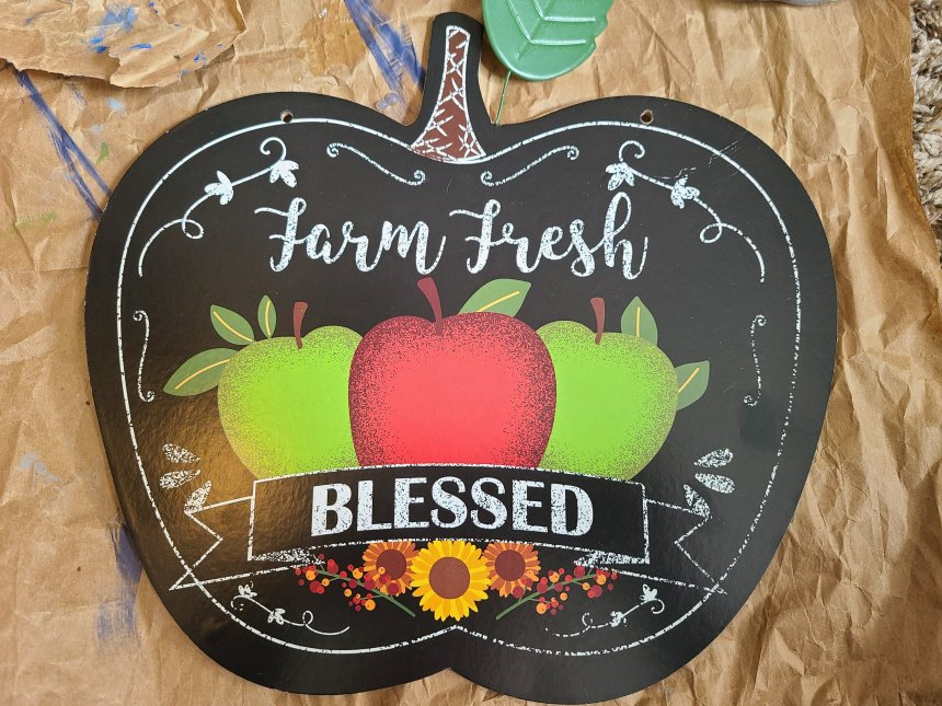"""Black apple shaped sign from Dollar Tree with """"Farm Fresh"""" and """"Blessed"""" written on it. This is the sign I used to create the teacher door hanger."""
