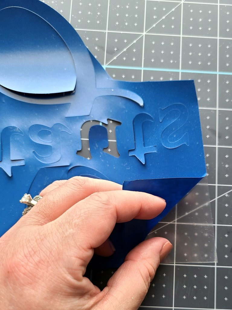 Weeding HTV by pulling excess blue vinyl from the design and backing. This split letter monogram will be used on the teacher door hanger.