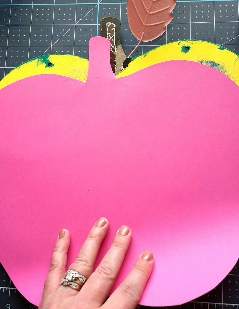 Pink cardstock cut to the size and shape of the teacher door hanger being placed on the back of it.