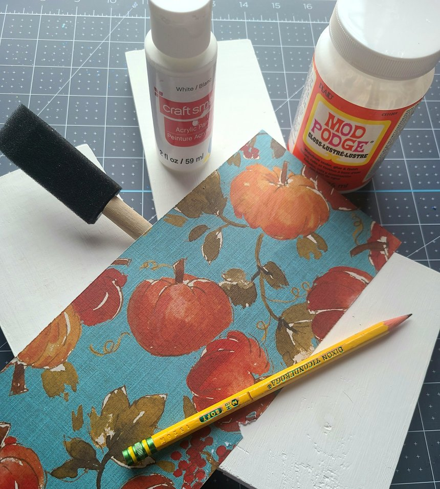 """Supplies I used for the reversible faux books: wood 6"""" long painted white (3), pencil, cardstock (aqua with orange pumpkins and green leaves), foam brush, white acrylic paint, and Mod Podge."""